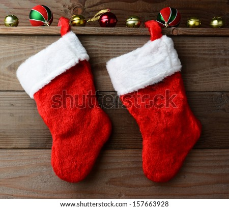 Christmas stockings hung on a rustic wooden wall with sleigh bells and ornaments. - stock photo