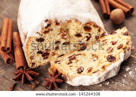 Christmas stollen and spices on wooden background. - stock photo