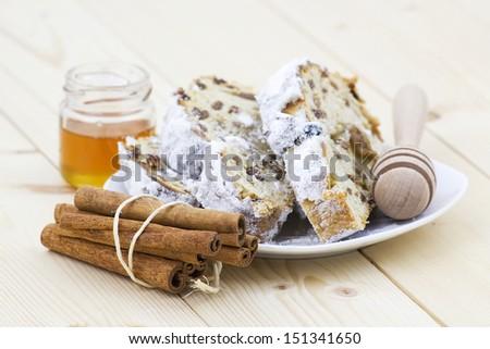 christmas stollen, honey and cinnamon sticks - stock photo