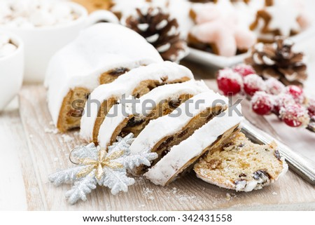 Christmas Stollen on a wooden board and cookies, closeup, horizontal - stock photo