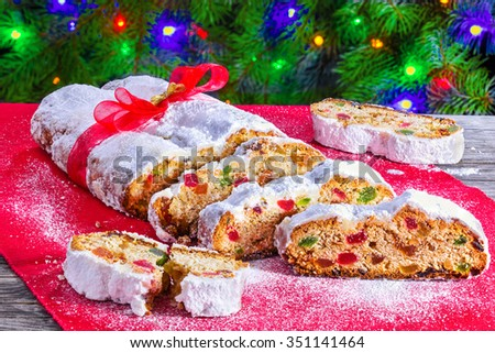 Christmas Stollen, traditional german christmas cake with dried fruits, nuts, spices and icing sugar decorated with red and gold ribbons, with bokeh background, horizontal close-up