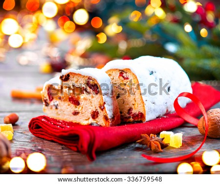 Christmas Stollen. Traditional Sweet Fruit Loaf with Icing Sugar. Xmas holiday table setting, decorated with garlands, baubles, wallnuts, hazelnuts, cinnamon sticks - stock photo