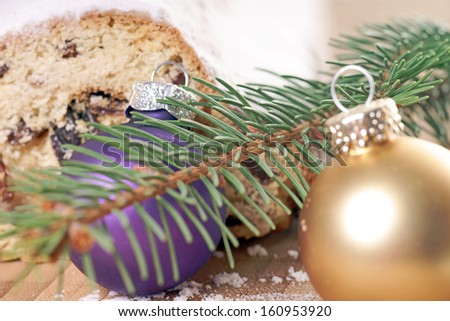 Christmas stollen with fir branch and christmas baubles / christmas time - stock photo