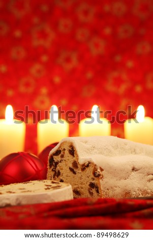 Christmas stollen with ornaments and candles on red background