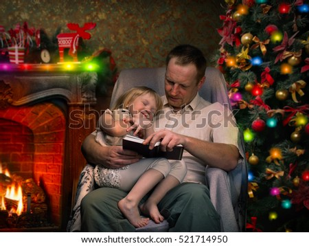 Christmas story by the fireplace. Dad reads a book a little daughter. Christmas tree, festive interior of the house. Christmas Eve