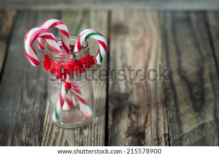christmas sweet candys in the glass on the wood background - stock photo