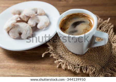 Christmas sweet rolls with coffee on brown wooden background. - stock photo
