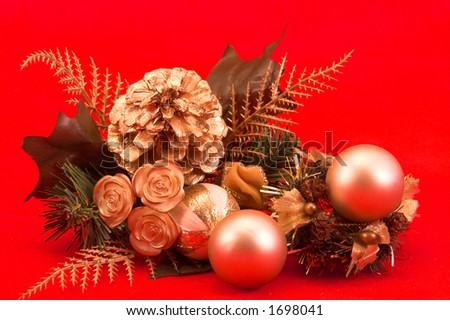 Christmas table centre / center piece with fir cones, mock greenery and gold baubles against a festive red background - stock photo