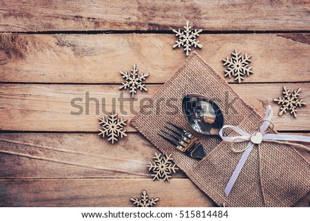 christmas table place setting and silverware, snowflakes on wooden background with space.