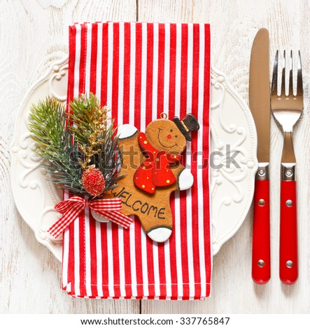 Christmas table place setting. Elegant empty plate, cutlery, candy cane napkin and funny gingerbread men.