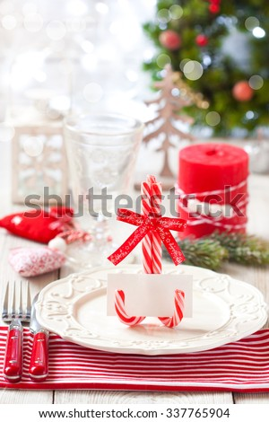 Christmas table place setting. Elegant empty plate, cutlery, napkin and blank name card on candy cane stand. - stock photo