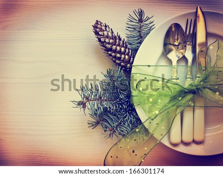 Christmas table place setting with christmas pine branches and plate, kine, fork ,ribbon and bow/ Christmas holidays background - stock photo
