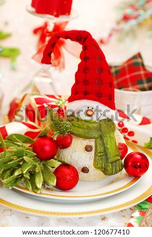christmas table set with funny snowman in red cap on the plate - stock photo