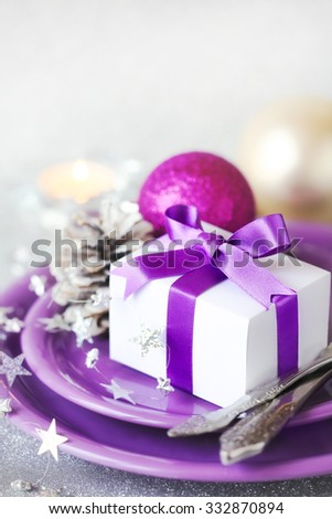 Christmas table setting - Christmas gift tied with purple ribbon on purple plates with festive decorations at the background with copyspace for your text - stock photo
