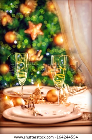 Christmas table setting, festive dinner still life and beautiful decorated Xmas tree at home, New Year eve, luxury wintertime party concept - stock photo