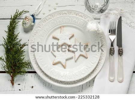 Christmas table setting from above - elegant white plate with cookies, natural pine tree branch on vintage planked wood. Rustic or vintage style. - stock photo