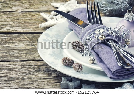 Christmas table setting in silver tone on wooden table - stock photo