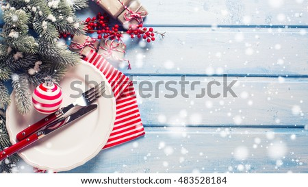 Christmas table setting. White plate, knife and fork, napkin and christmas decorations in white and red colors on blue wooden table. Top view. Drawn snow. Selective focus. Place for text.