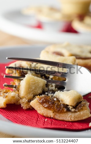 Christmas table setting with a plated serving of Mince Pie on red napkin, broken open with fork as if  eating in progress.  Pile of uneaten pies in soft focus background.