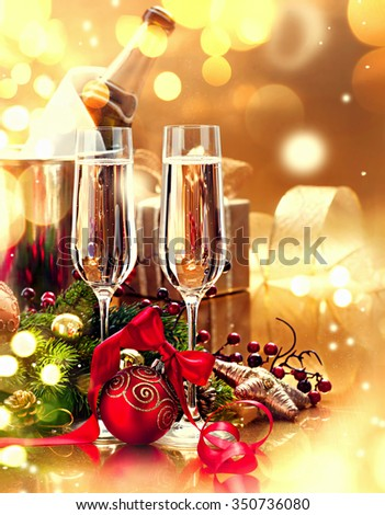 Christmas table setting with Champagne. New Year and Christmas celebration. Two Champagne Glasses and holiday decoration over golden background