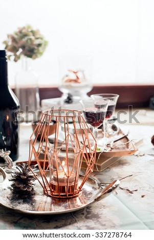 Christmas table setting with decorations and glasses of port wine/sherry. Classic/modern style accessories. Natural light photo. Shallow focus on the candle. Toned photo.