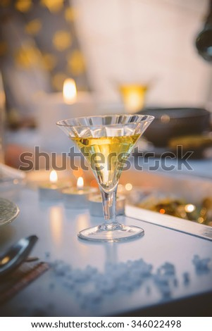 Christmas table setting  with elegant glasses of white wine. Decorative table with candles and shiny ornaments on the middle.Rustic or vintage style/Christmas decorative table with white wine served