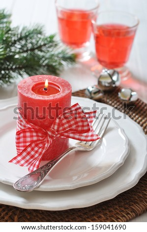 Christmas table setting with red candle and fir tree branch - stock photo