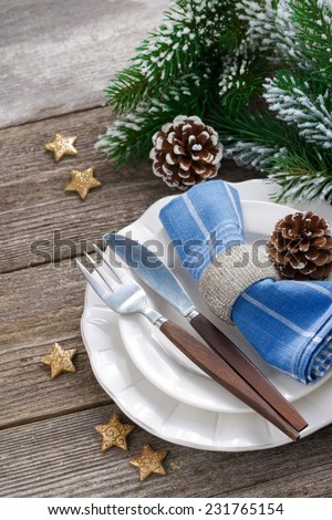 Christmas table setting with spruce branches on a wooden background, vertical, top view, close-up - stock photo