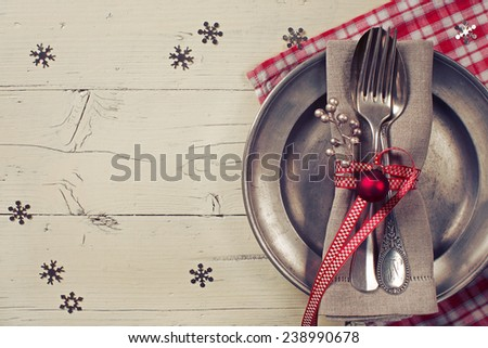 christmas table setting with vintage tin plate and silverware on a cream-colored table - stock photo