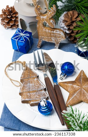 Christmas table setting with wooden decorations and spruce branches, close-up, vertical - stock photo