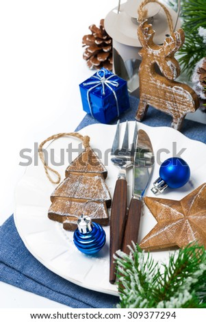 Christmas table setting with wooden decorations and spruce branches, top view, vertical - stock photo