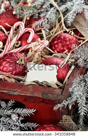 Christmas tag over Christmas ornaments and candy canes packed in an old antique wooden box with snow covered pine boughs surrounding them. Extreme shallow depth of field with selective focus on tag. - stock photo