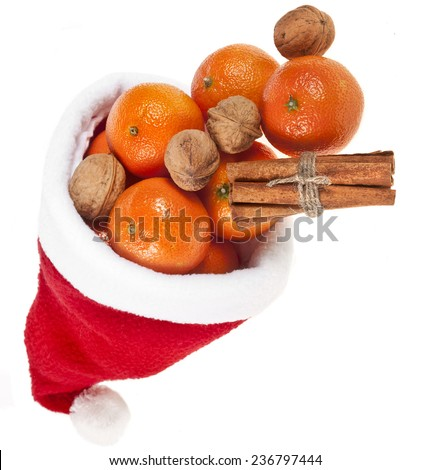 Christmas tangerines and nuts in a Santa Claus hat`s  isolated on a white background - stock photo