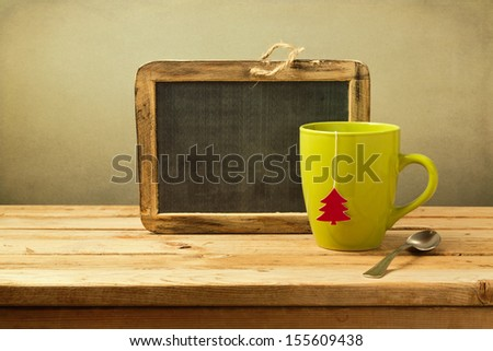 Christmas tea cup and chalkboard on wooden table - stock photo