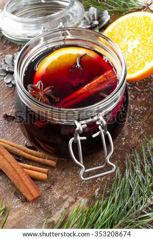 Christmas tea with orange fruit, anise, cinnamon and cloves on wooden table