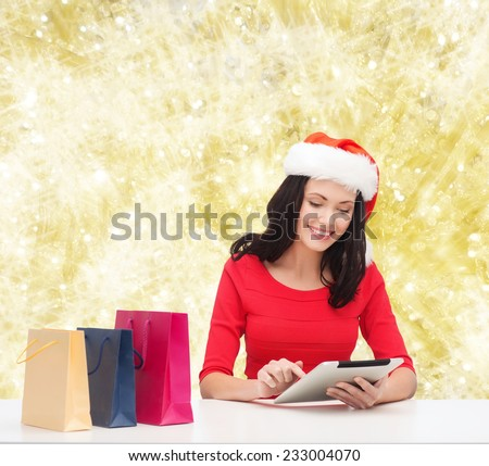 christmas, technology and people concept - smiling woman in santa helper hat with shopping bags and tablet pc computer over yelolow lights background - stock photo