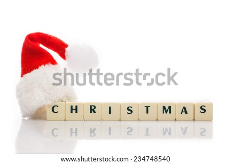 Christmas text spelled with dices, with santa hat. Isolated on white background with reflection. Room for text, copy space. - stock photo
