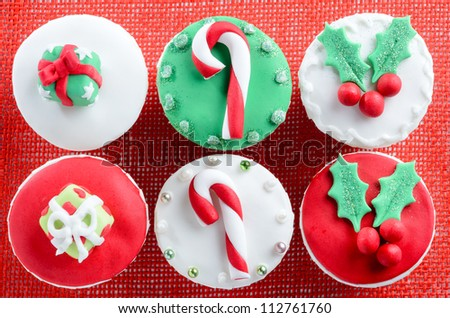 Christmas theme cupcakes in traditional red green colours and elements presents gifts candy cane mistletoe from overhead - stock photo