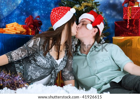 Christmas theme: happy young people in Santas caps kissing together.