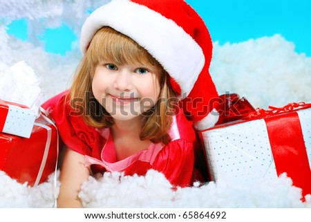 Christmas theme: little girl in santa hat lying on snow with presents.
