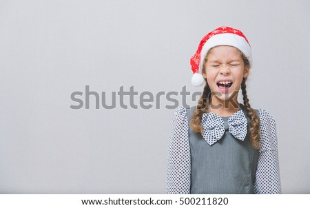 Christmas theme. Multi-ethnic girl in santa claus really wants gifts. Gray background.