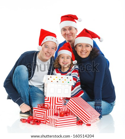 Christmas theme - Portrait of friendly family in Santa's hat with gift box, isolated on white - stock photo