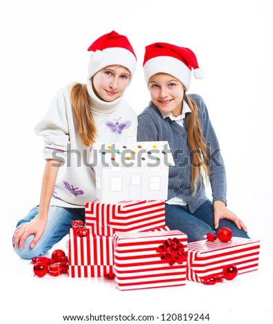 Christmas theme - Smiling happy two girs in Santa's hat with gift box and gingerbread house, isolated on white - stock photo
