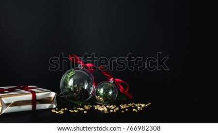 Christmas themed photo with blank space-clear glass Christmas balls with fir branches and pine cones inside, wrapped gift on a black background