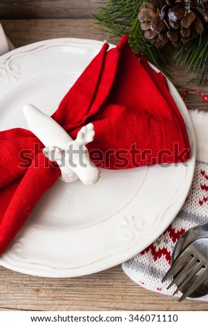 Christmas themed table setting with plate, utensils christmas wreath and chandelier on the background