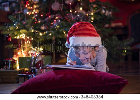 Christmas time, a little boy with a santa hat lying on a cushion is thinking to write his wish list to santa claus, at background the christmas tree illuminated with gifts on the floor - stock photo