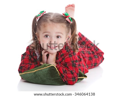 Christmas time.  Adorable preschooler wearing her Christmas pajamas and lying on a green pillow.  Isolated on white with room for your text.. - stock photo