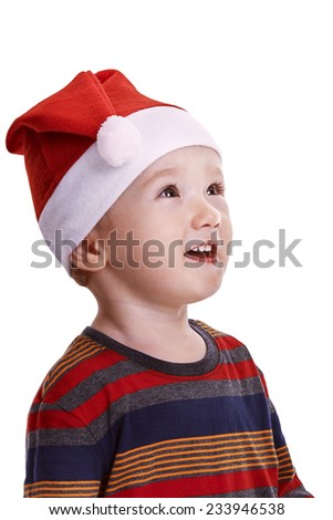 Christmas time: Baby boy isolated on white, with a Santa cap,  looking amazed to the side - stock photo