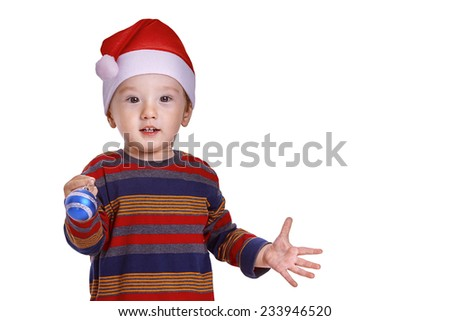 Christmas time: Baby boy with a Santa cap looking amazed and holding a blue Christmas decoration - stock photo