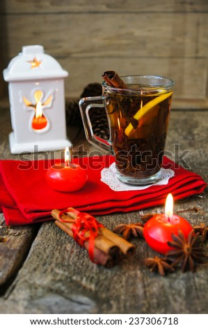 Christmas time, cup of tea with cinnamon and anise spices, festive decoration and candles - stock photo